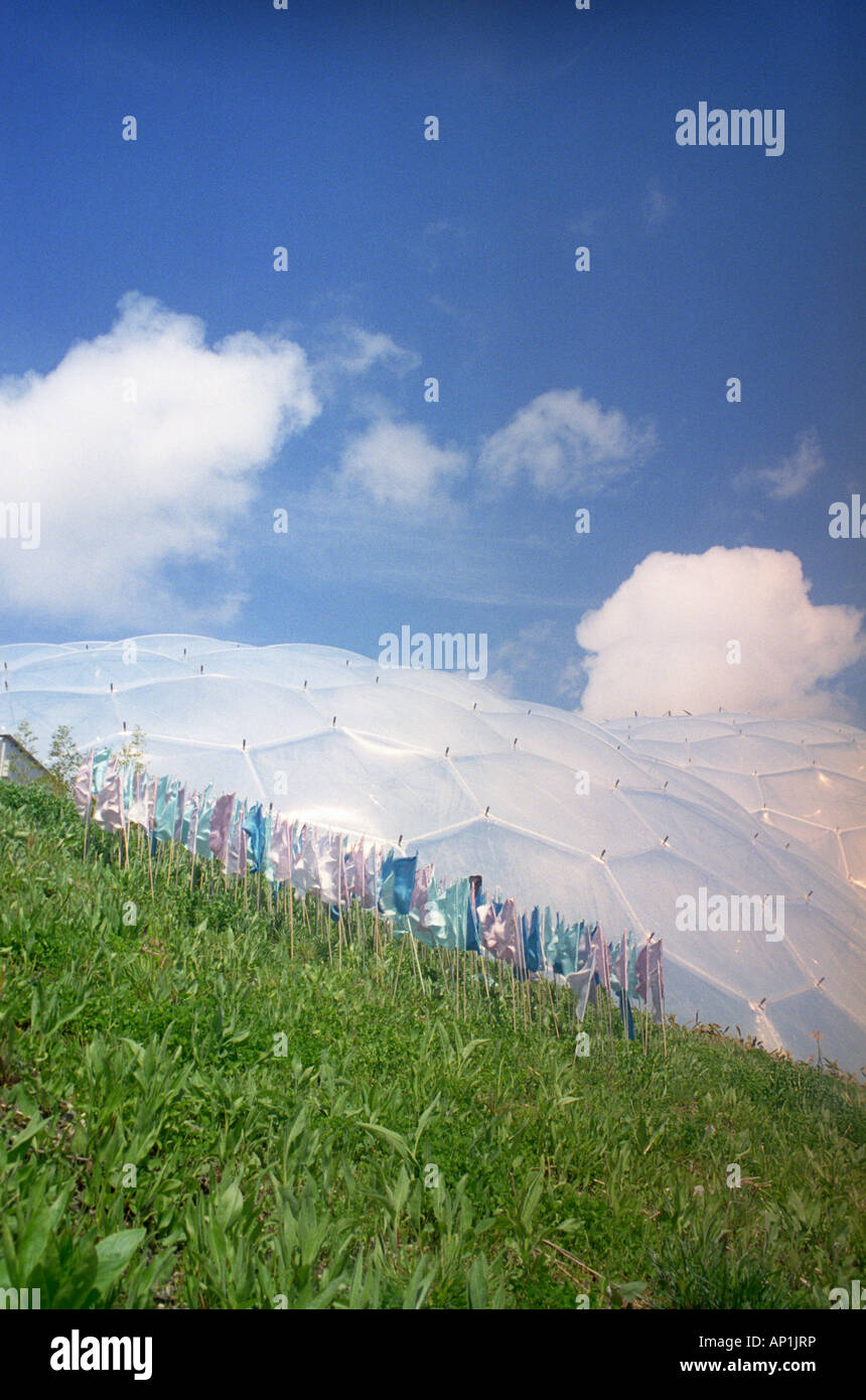 Colourful prayer flags display in front of a biodome at the Eden Project, Cornwall Stock Photo
