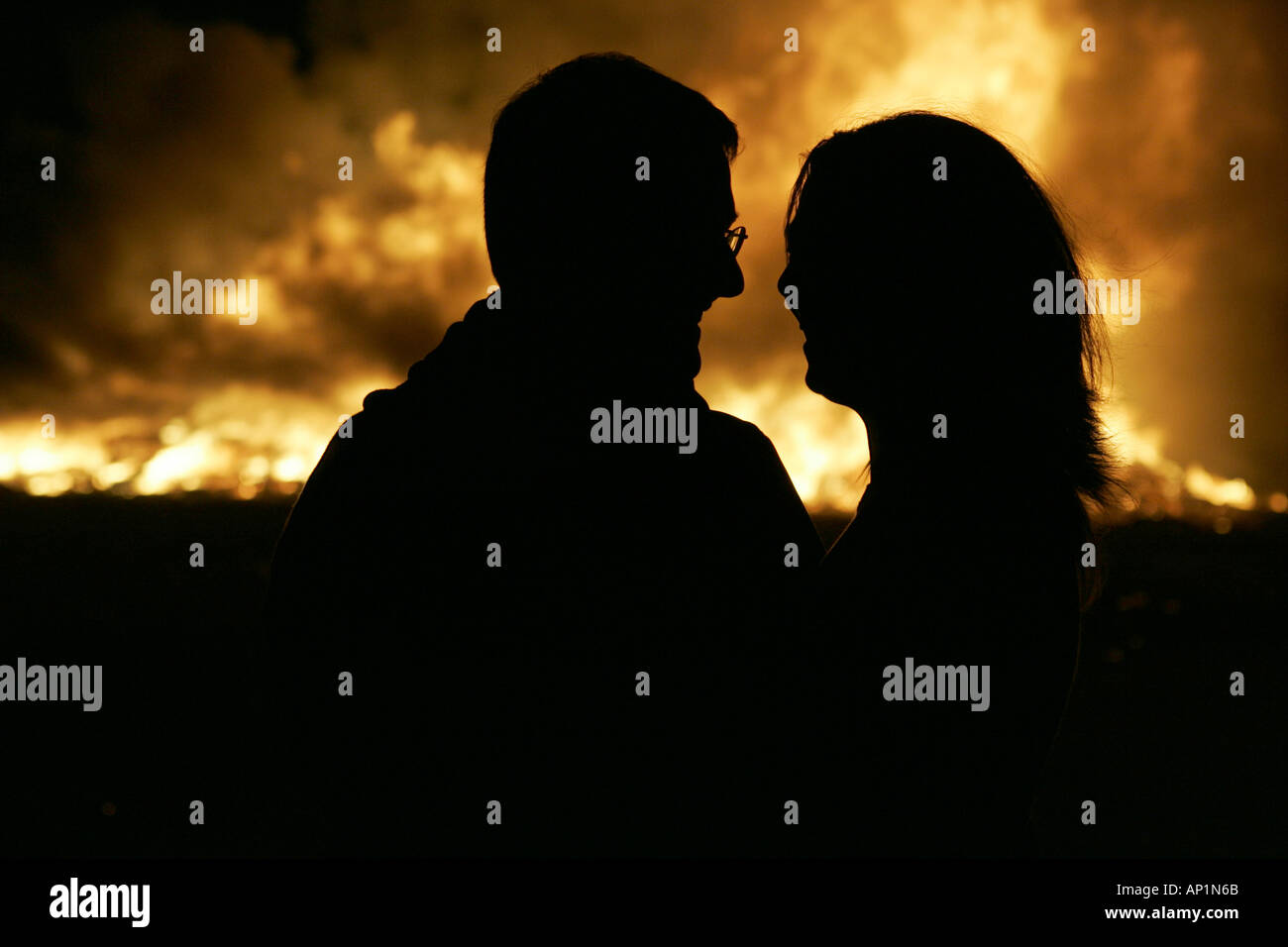 couple in front of night bonfire - Stock Image