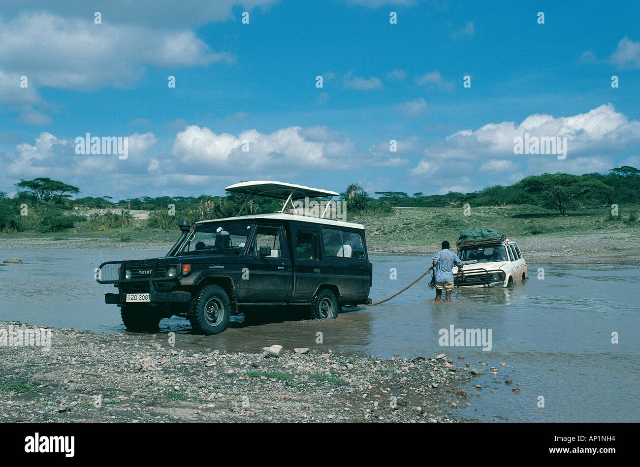 Toyota Landcruiser being prepared to tow another vehicle out of the Ol Duvai River in northern Tanzania East Africa - Stock Image