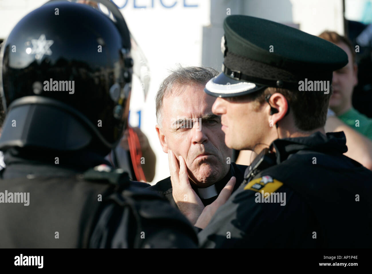 Fr Aidan troy talks to PSNI officers on crumlin road at ardoyne shops belfast 12th July - Stock Image