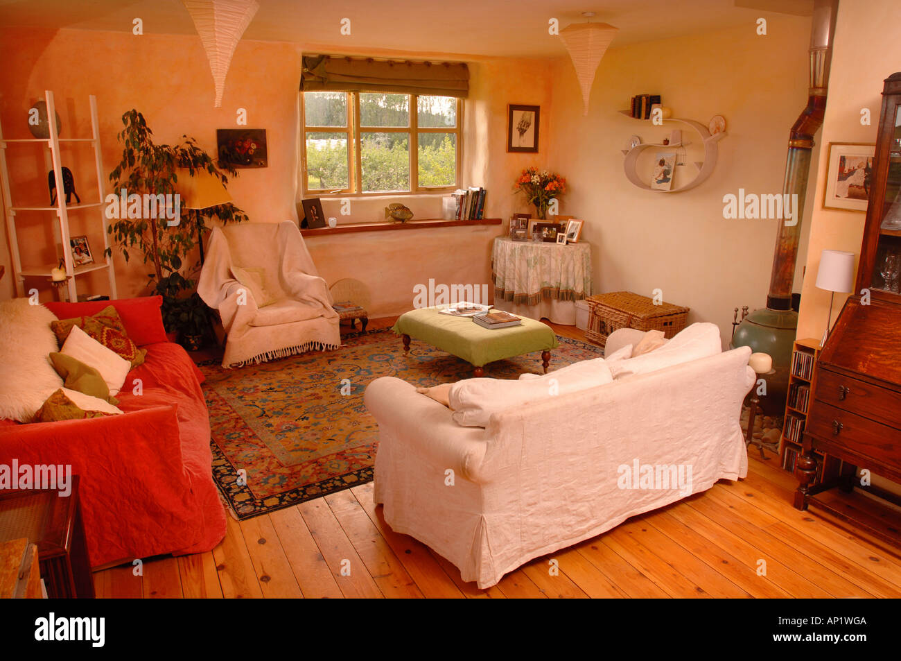 THE LIVING ROOM IN A HOUSE BUILT WITH STRAW BALE WALLS WITH A RENDERED COVERING GLOUCESTERSHIRE UK - Stock Image