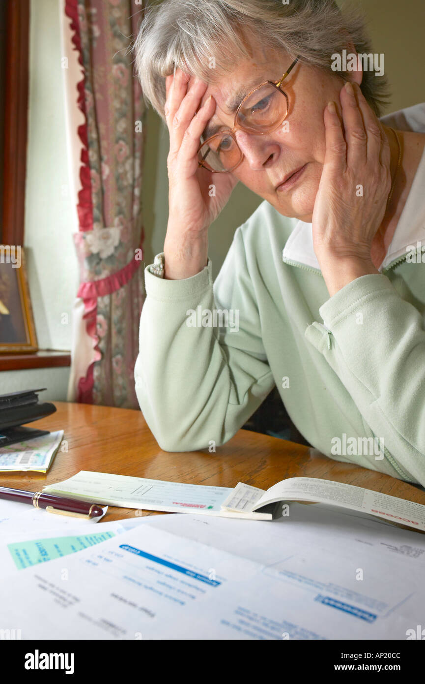 Old age pensioner sitting down holding head worrying about money and bills to be paid - Stock Image