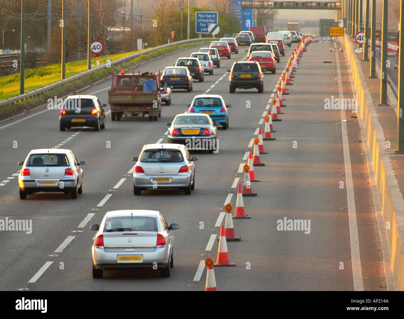 Roadworks lane closure on motorway in UK england united kingdom britain highway road repair cones lanes - Stock Image