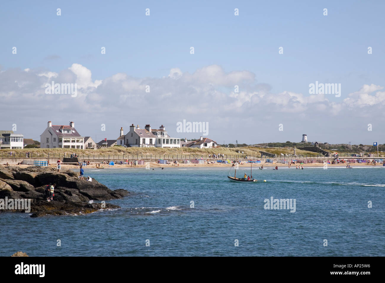 Trearddur Bay beach busy with tourists from rocks on sunny blue sky day in summer. Trearddur Isle of Anglesey North Wales UK - Stock Image