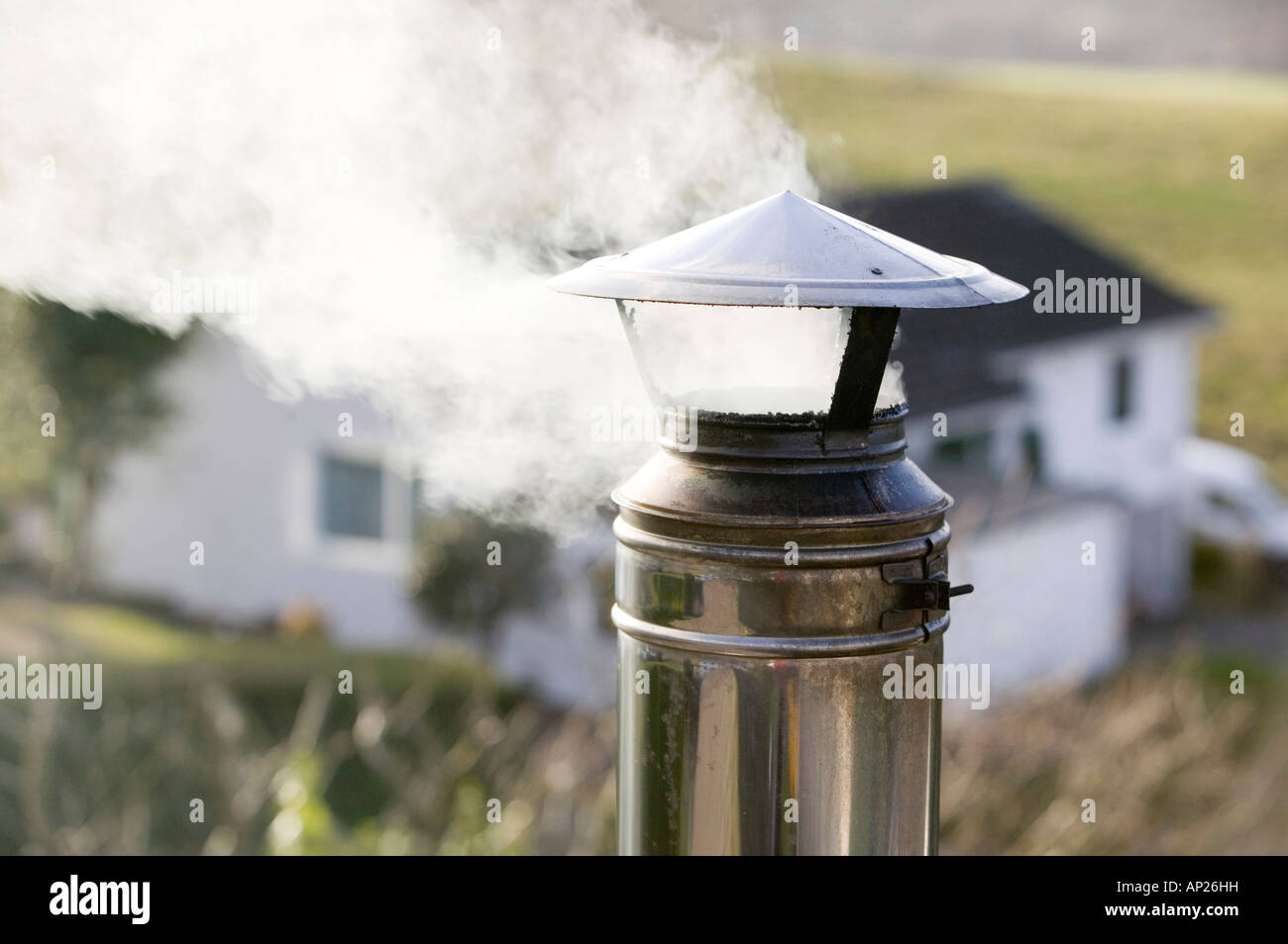 A household chimney emmiting smoke - Stock Image