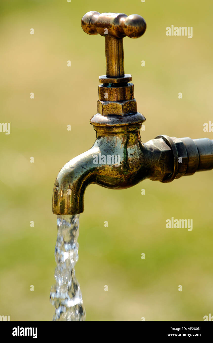 an old fashioned style of brass water tap outside oudoors running wasting water turned and left on running - Stock Image