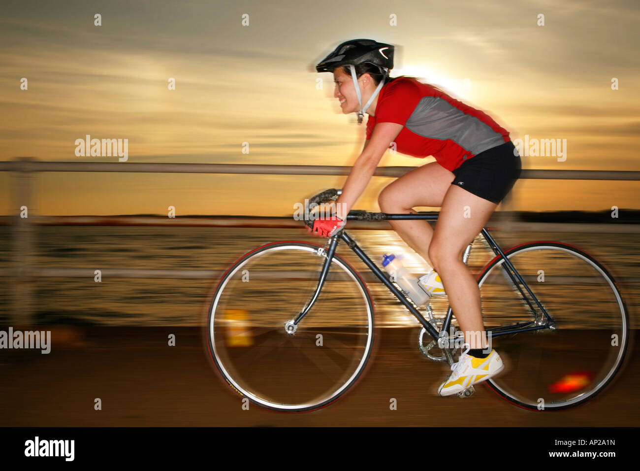 Young woman 26 years old ridding bicycle sunset, MR-09-30-2007 - Stock Image