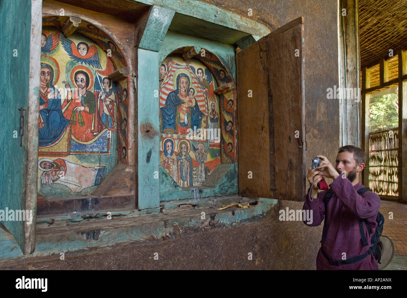 A tourist taking photographs inside the Ura - Kidane Mihret Monastery which can be visited by taking a boat from - Stock Image