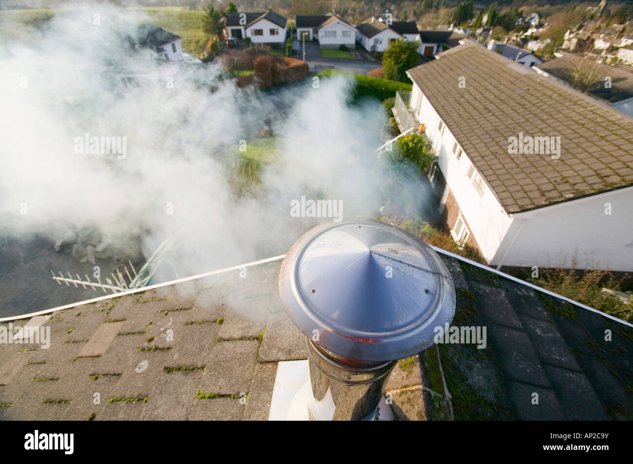 A household chimney emmiting smoke Stock Photo