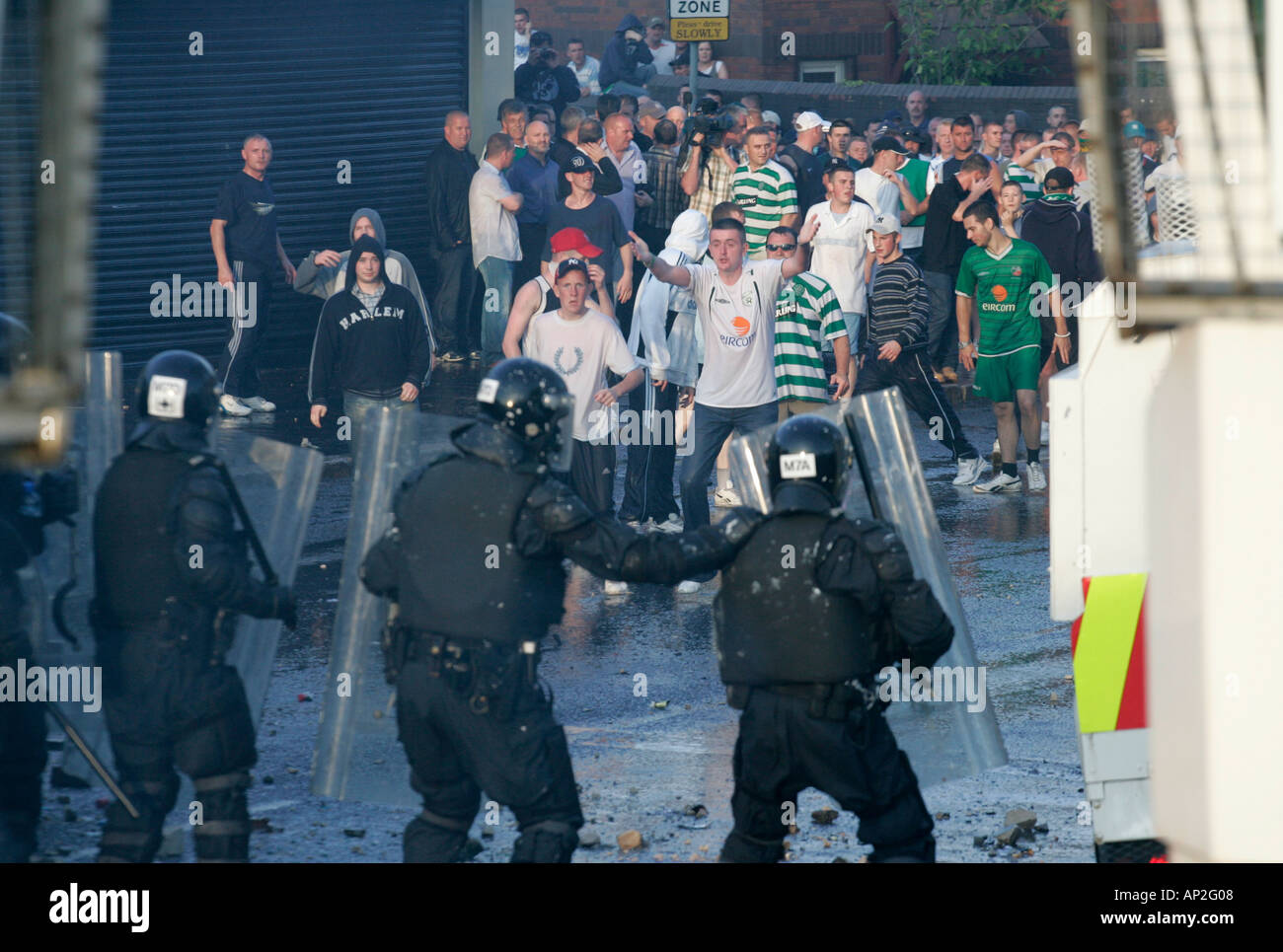 PSNI riot police face angry mob of rioters on crumlin road at ardoyne shops belfast 12th July - Stock Image
