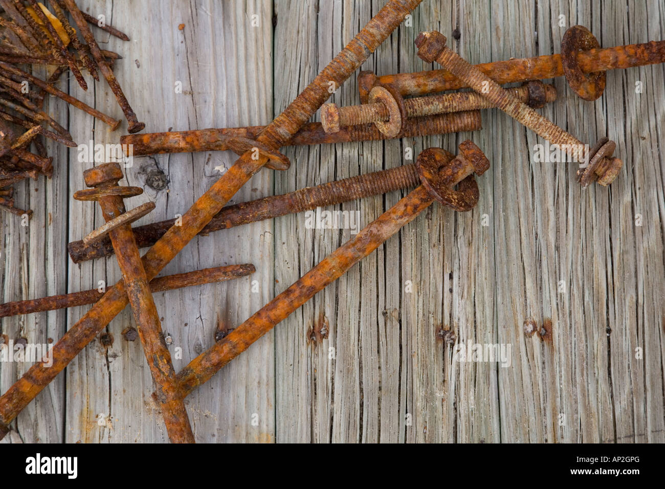 Rusty nails laying on weathered wood - Stock Image