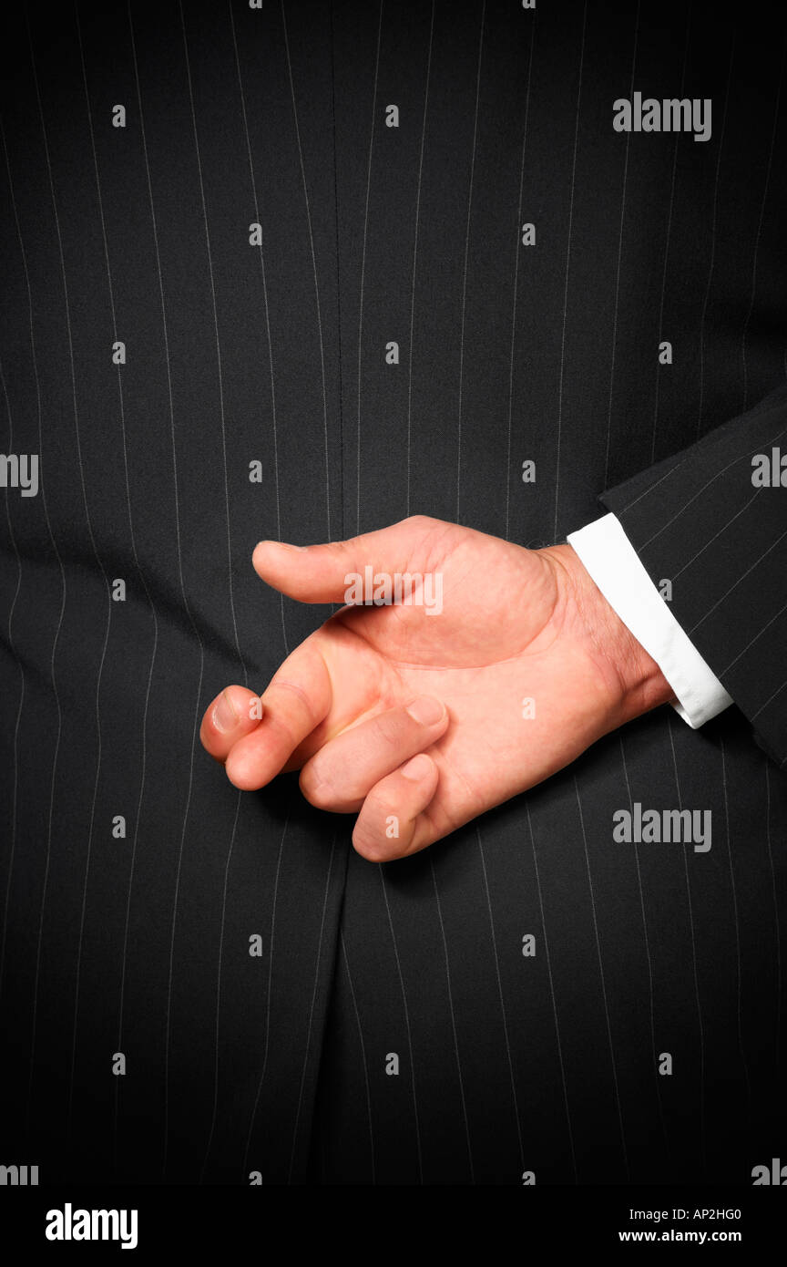 BUSINESS MAN WEARING DARK PINSTRIPE SUIT WITH FINGERS OF RIGHT HAND CROSSED BEHIND BACK - Stock Image
