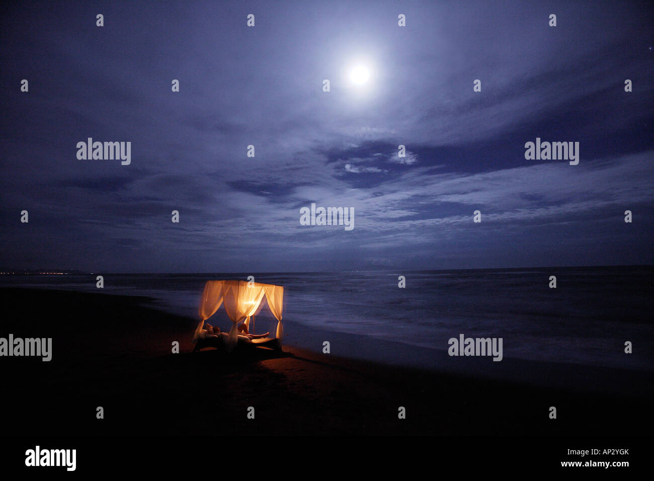 Illuminated four-poster bed standing on the beach at night, Bali, Indonesia - Stock Image