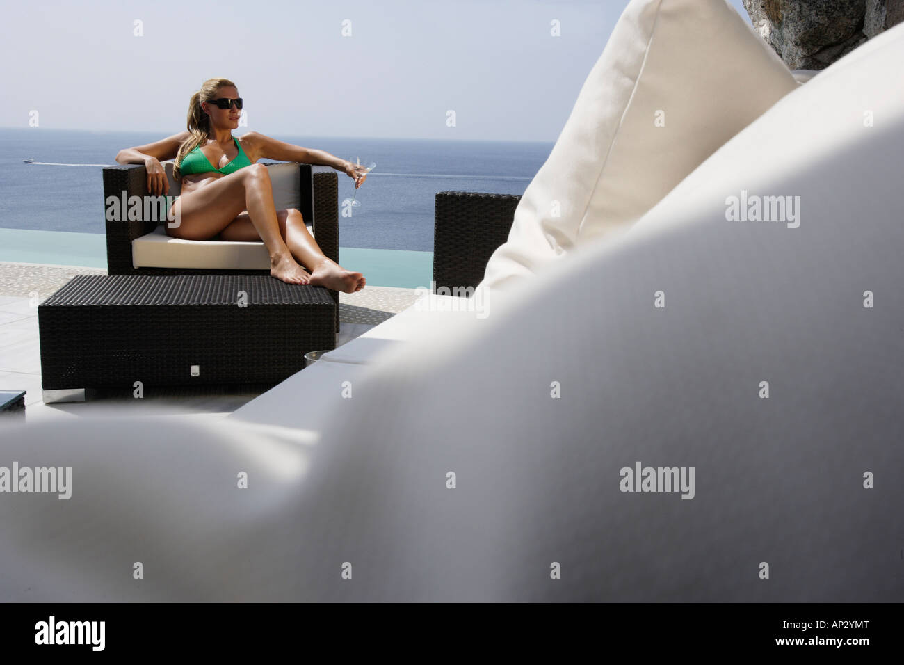 Woman sunbathing on a chair and drinking a cocktail, near Uluwatu, Bali, Indonesien - Stock Image