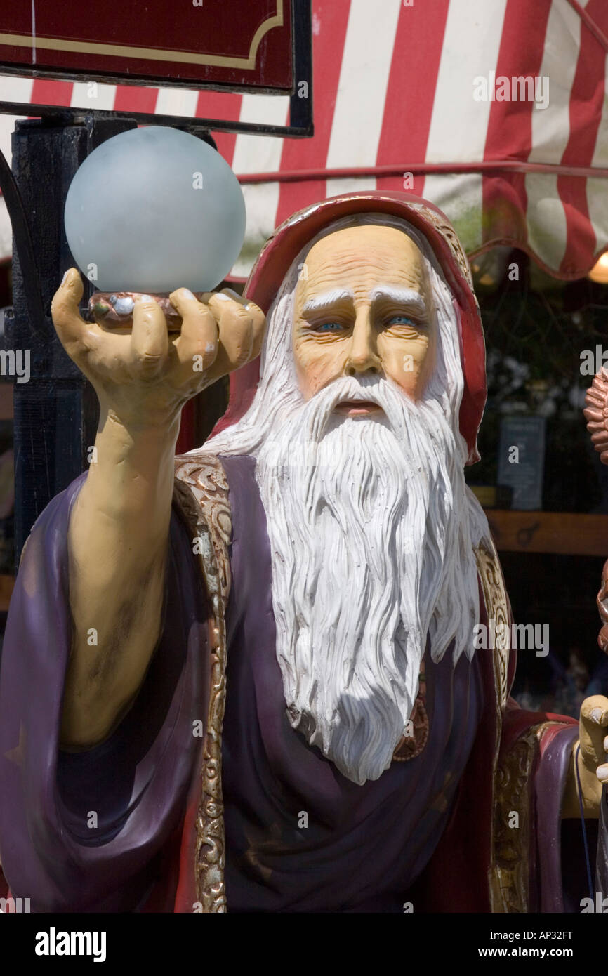 A plastic figure of the famous wizard Merlin holding an orb outside a gift shop in Tintagel - Stock Image