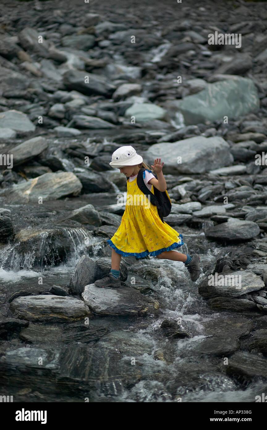 Girl crossing melting water, hiking at Franz Josef Glacier, Westland National Park, Westcoast, South Island, New Stock Photo
