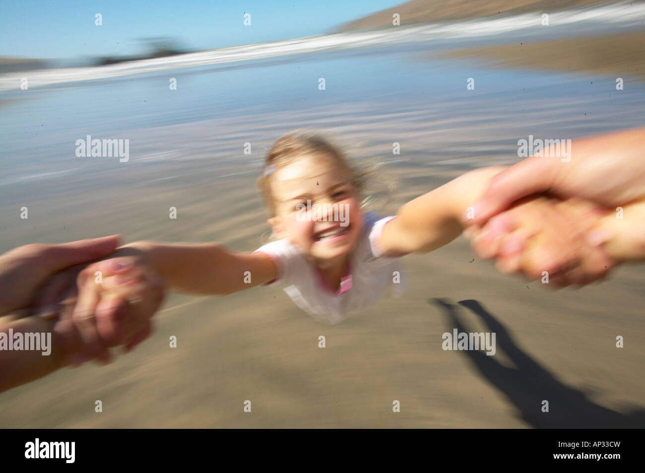 Girl (5 y.) turning around her father (flying merry go round), at Okains Bay, Bank`s Peninsula, east coast, South Stock Photo