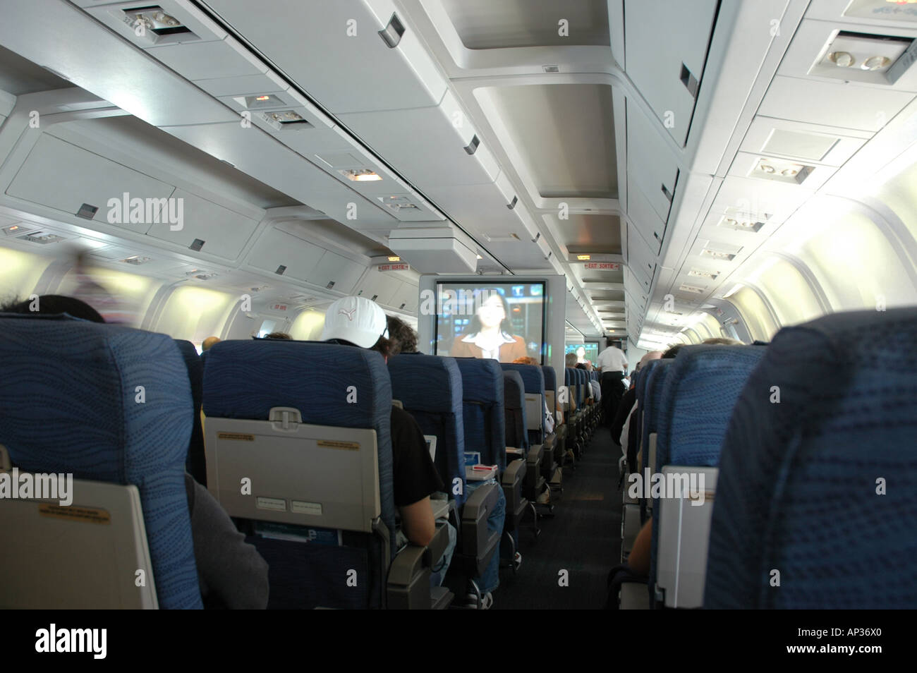 Interior of wide-bodied passenger aircraft cabin. - Stock Image