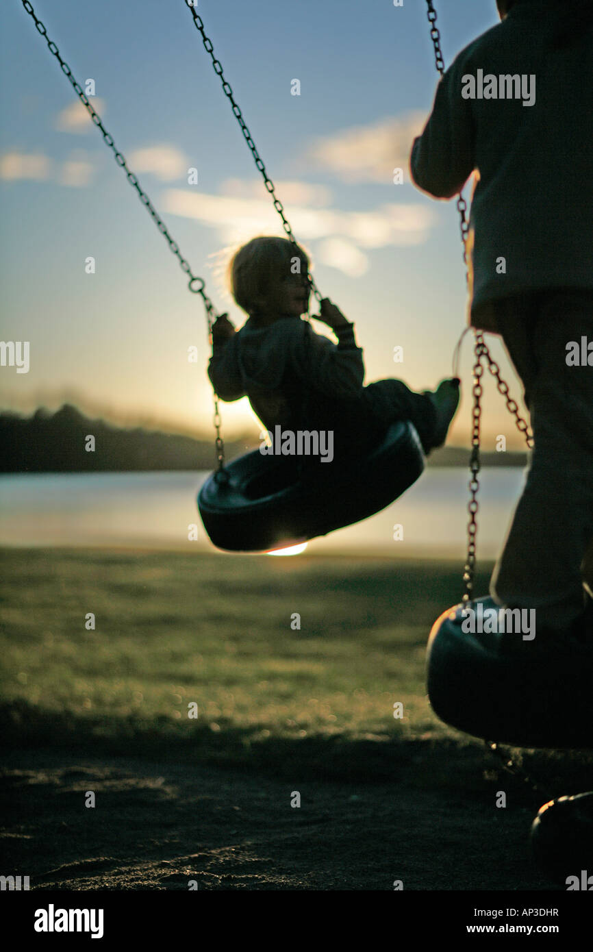 Children on a swing near the lakeshore, Madkroken, Smaland, Sweden - Stock Image