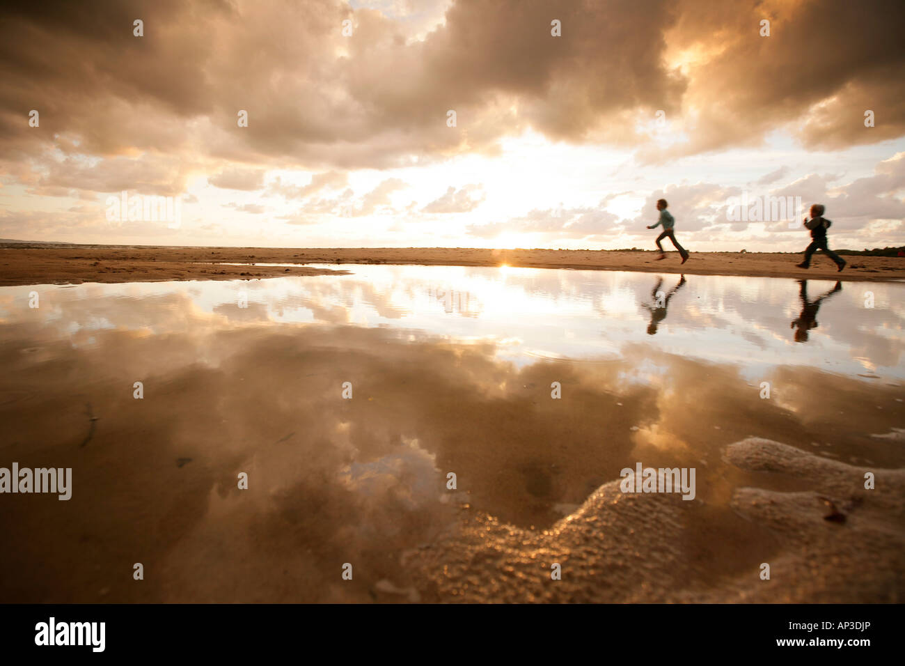 Two children running along the beach on a cloudy day, Reflection, Segeltorpstrandet, Halmstadt, Skane, Sweden Stock Photo