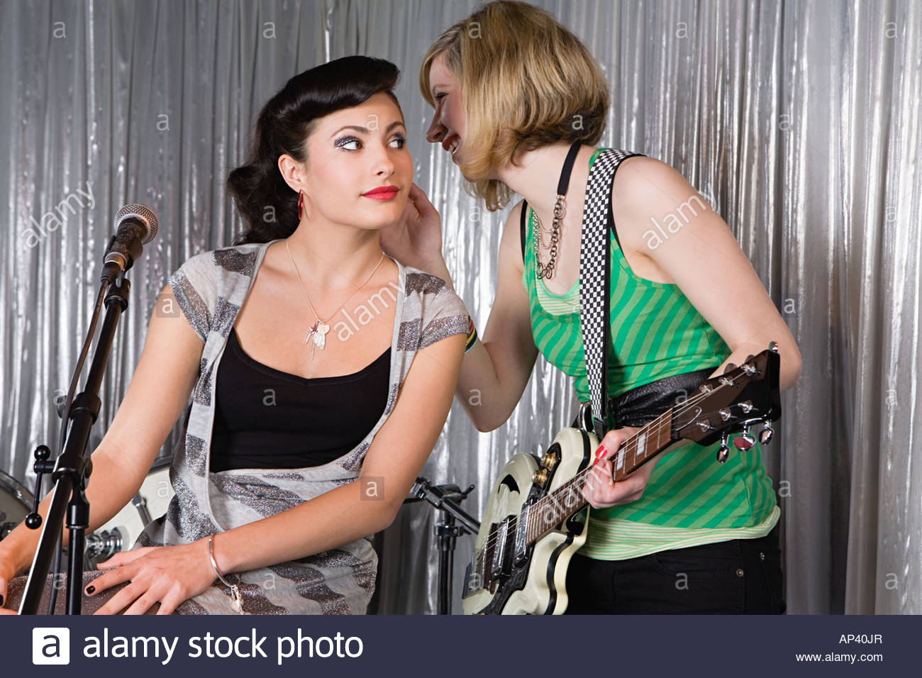 Two young women whispering - Stock Image