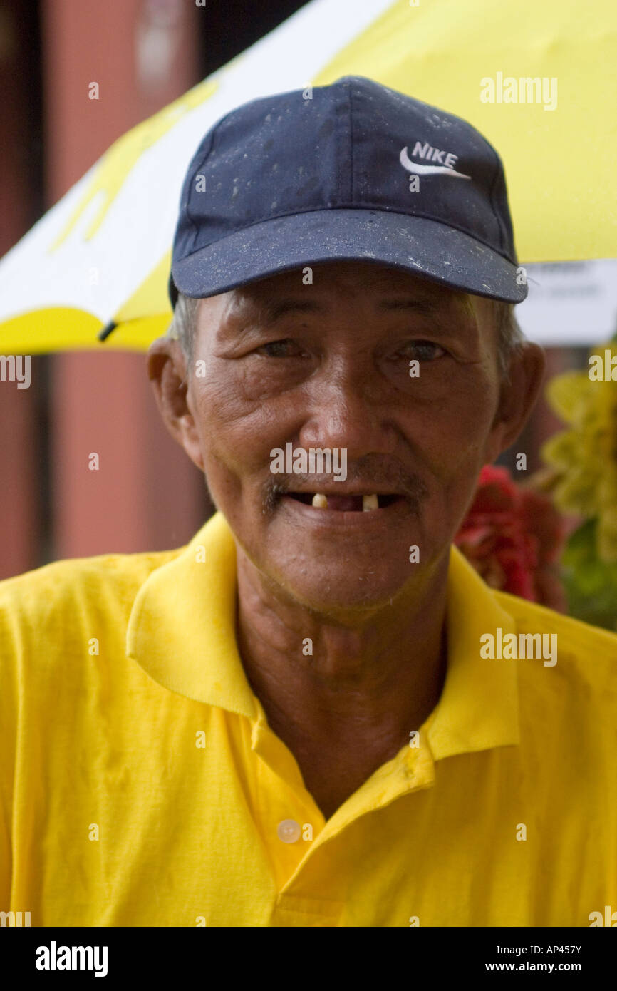 A yellow-shirted cycle-rickshaw driver grins. He plies his trade in Melaka City, Malaysia. - Stock Image