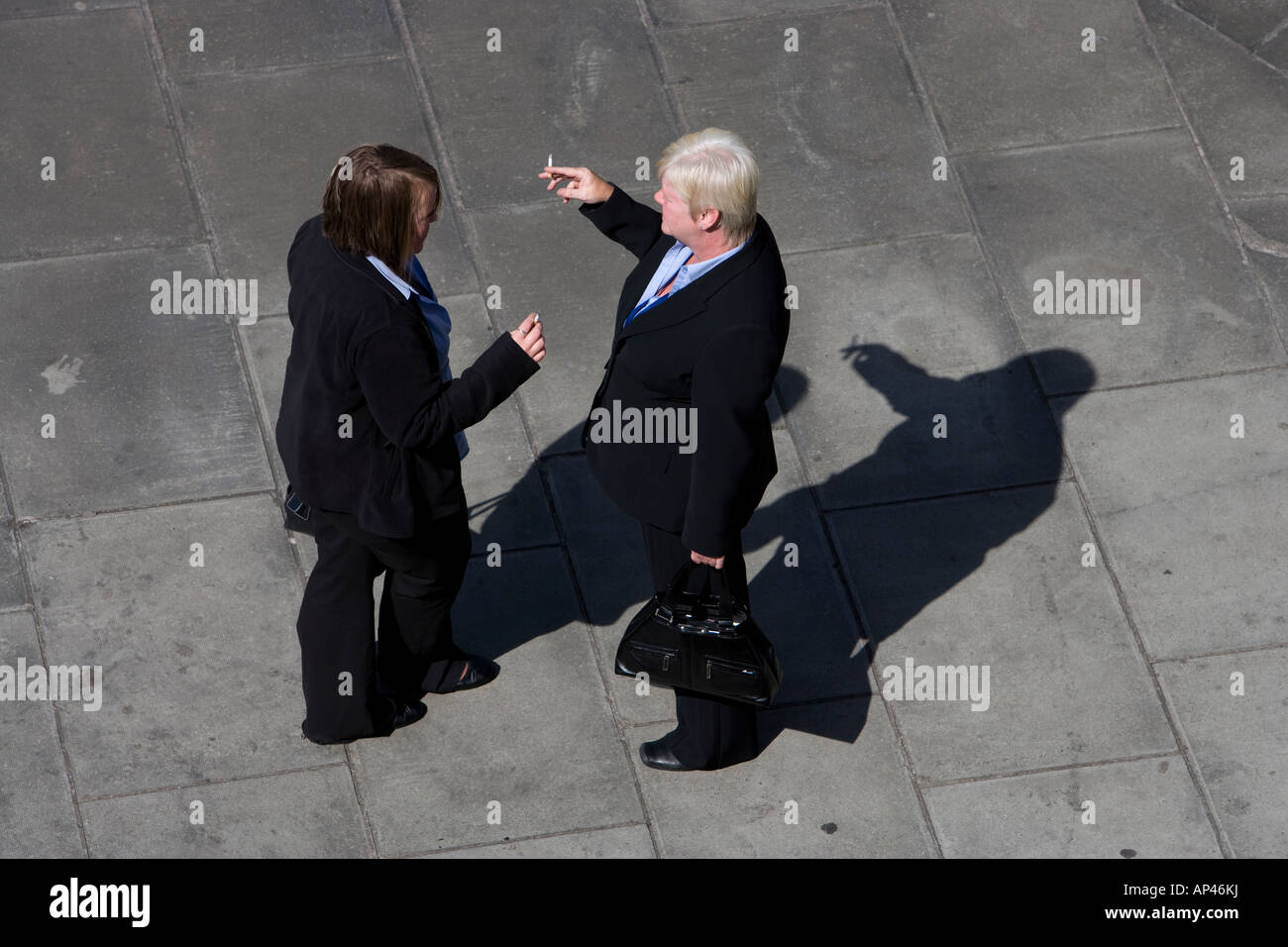 Two Women Dressed In Black Business Suits Talking And Smoking Stock