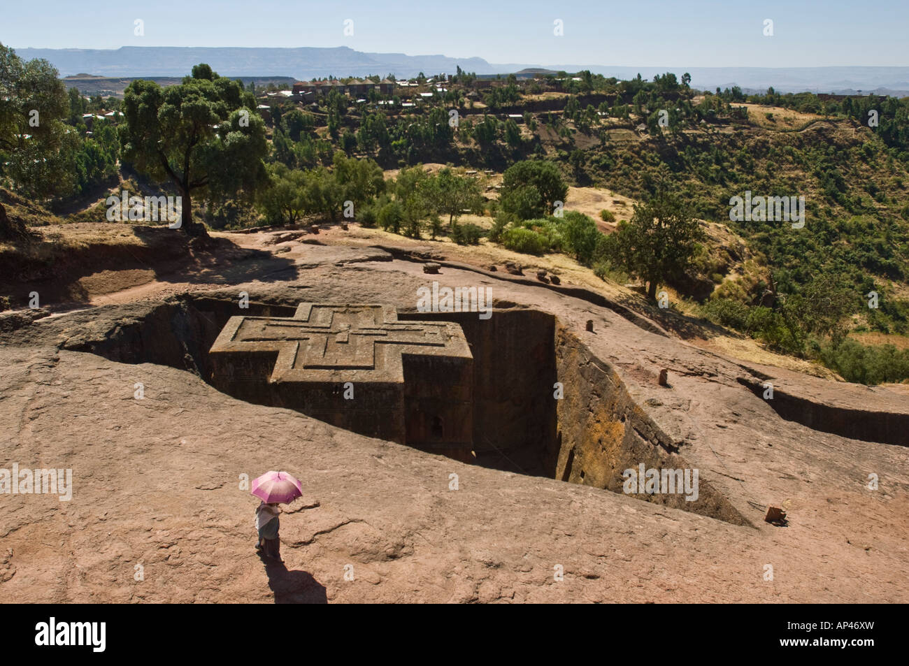 A lone local woman with a pink umbrella looks over the Bete Giyorgis or Church of St. George monolithic church in - Stock Image