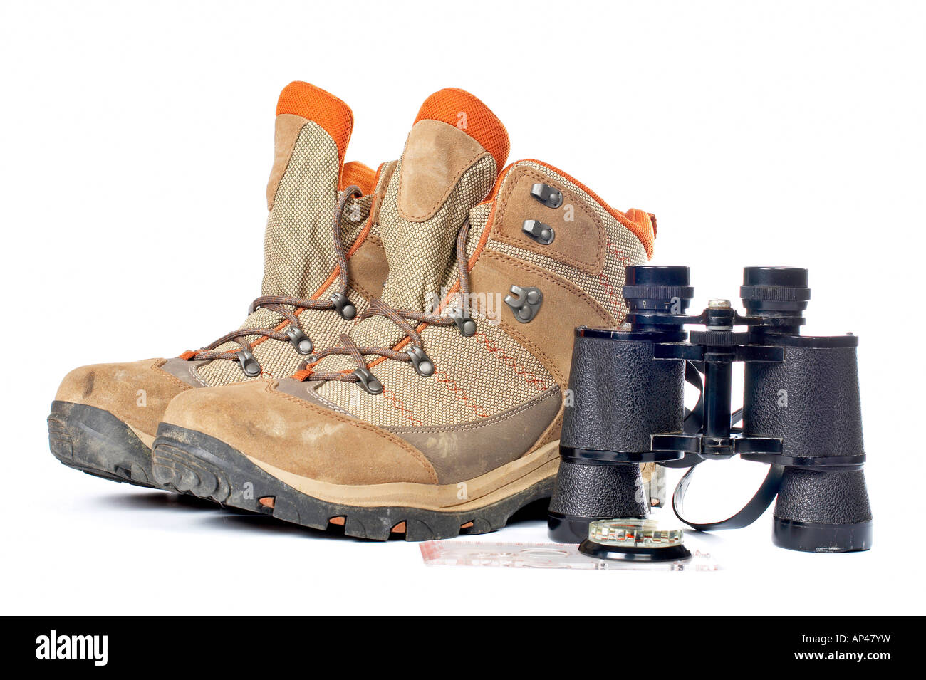 Hiking boots compass and binoculars on a white background - Stock Image