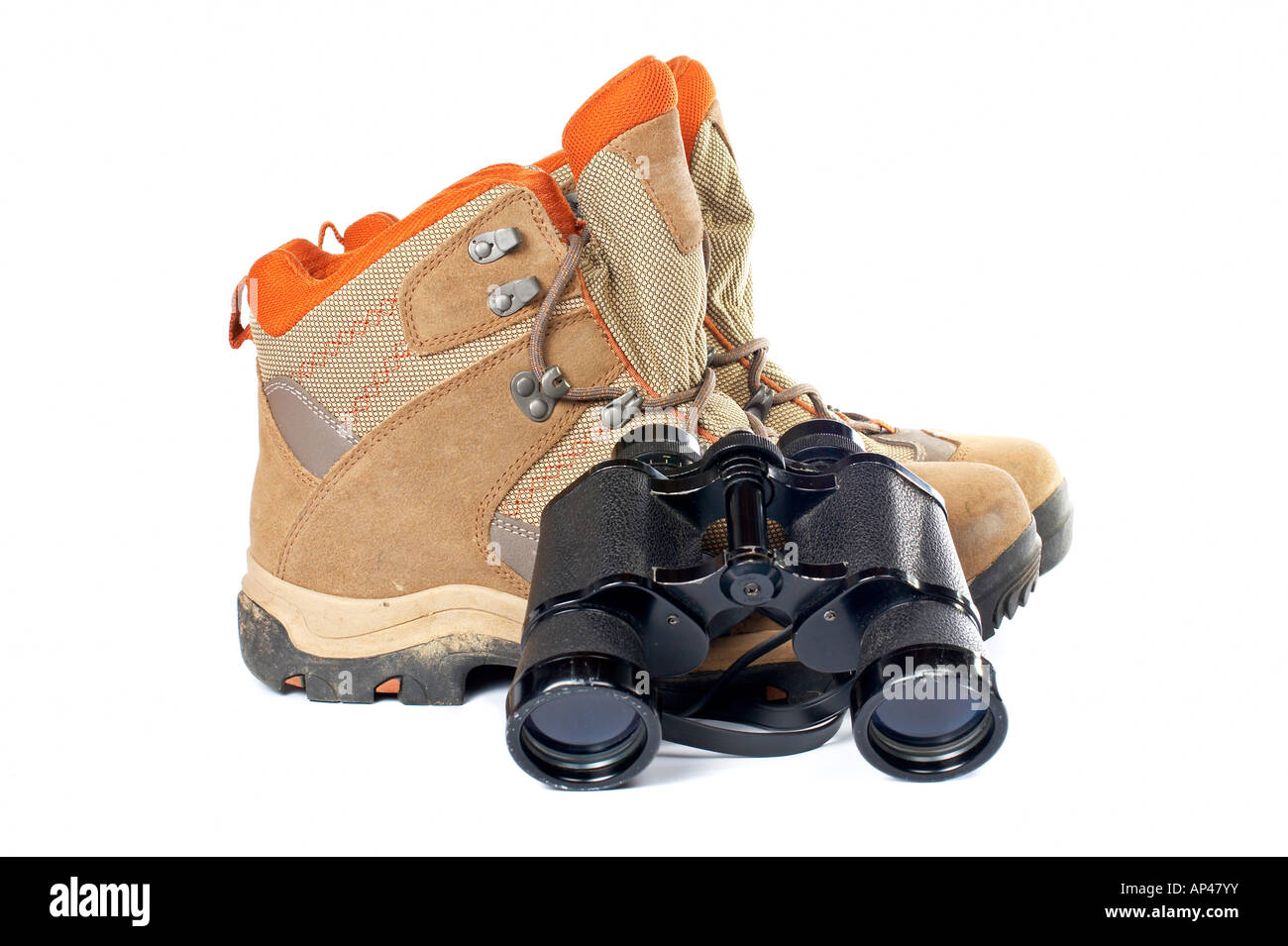 Used hiking boots and binoculars with soft shadow on white background - Stock Image