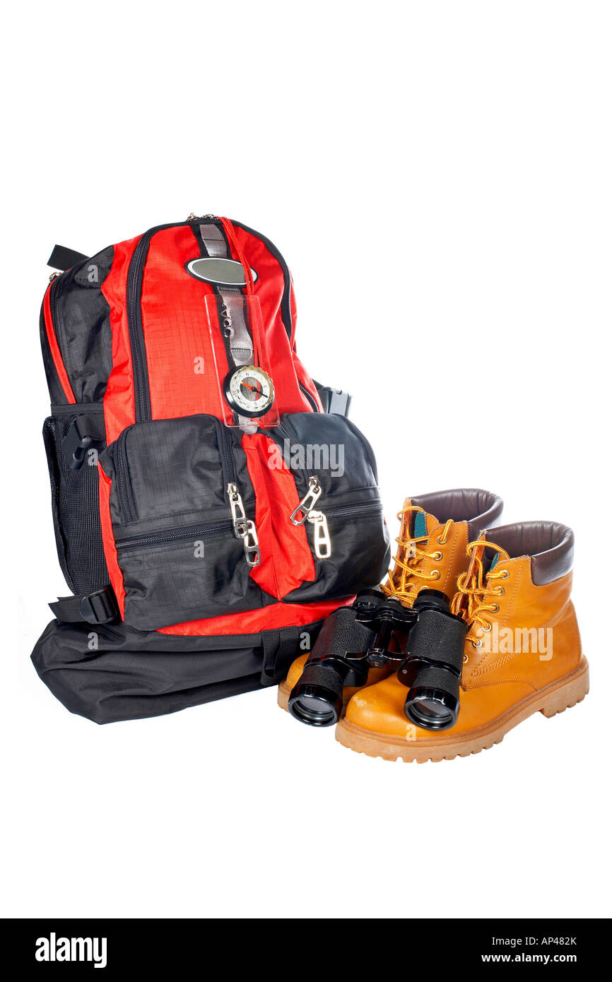 Hiking boots compass binoculars and backpack over a white background - Stock Image