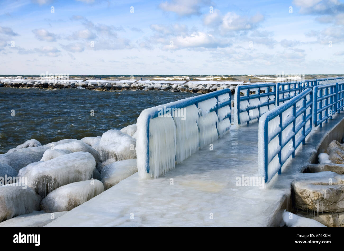 Lake Michigan cold winter spray creates ice on the pier and walkway at Holland Harbor - Stock Image