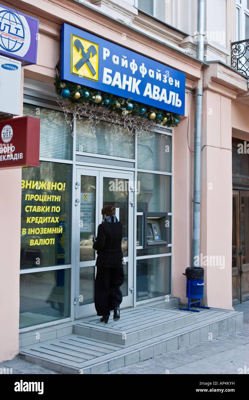 A woman goes inside a Raiffeisen Bank Aval branch in Kiev, Ukraine - Stock Image