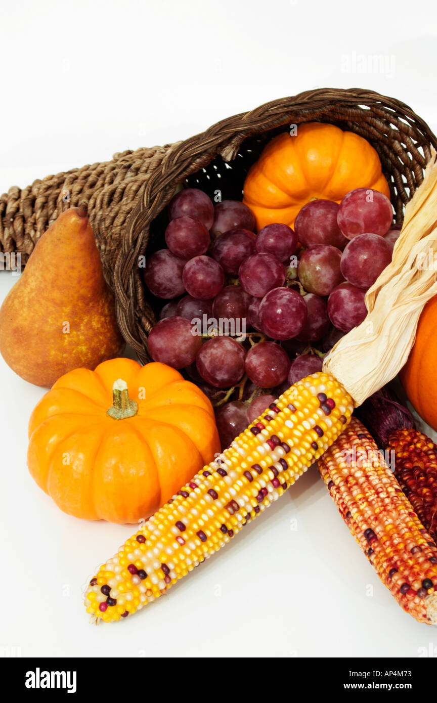 Close up view of Thanksgiving harvest scene with cornucopia isolated against white background - Stock Image