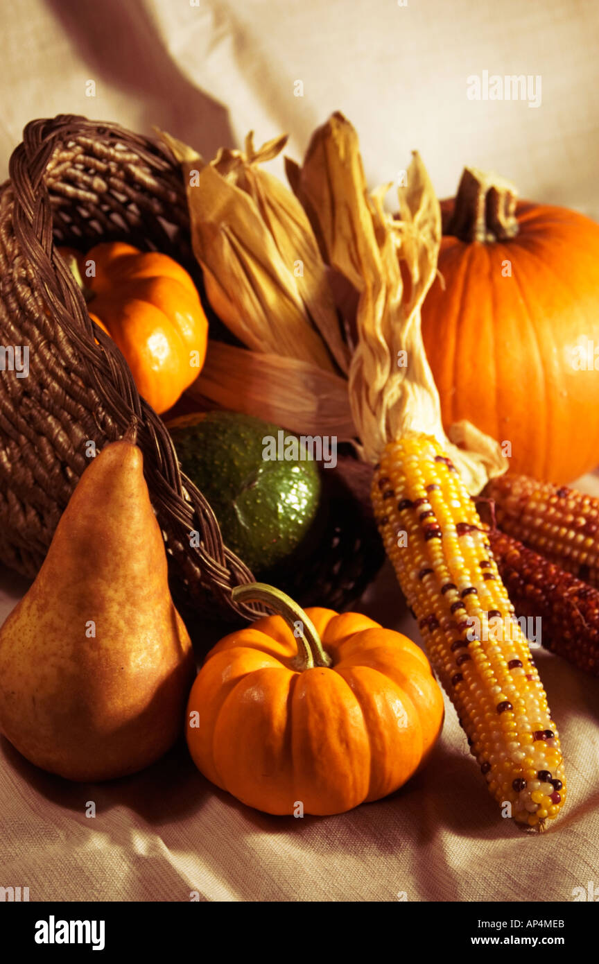 Warm toned autumn harvest scene featuring pumpkin corn and other fruits and vegetables - Stock Image