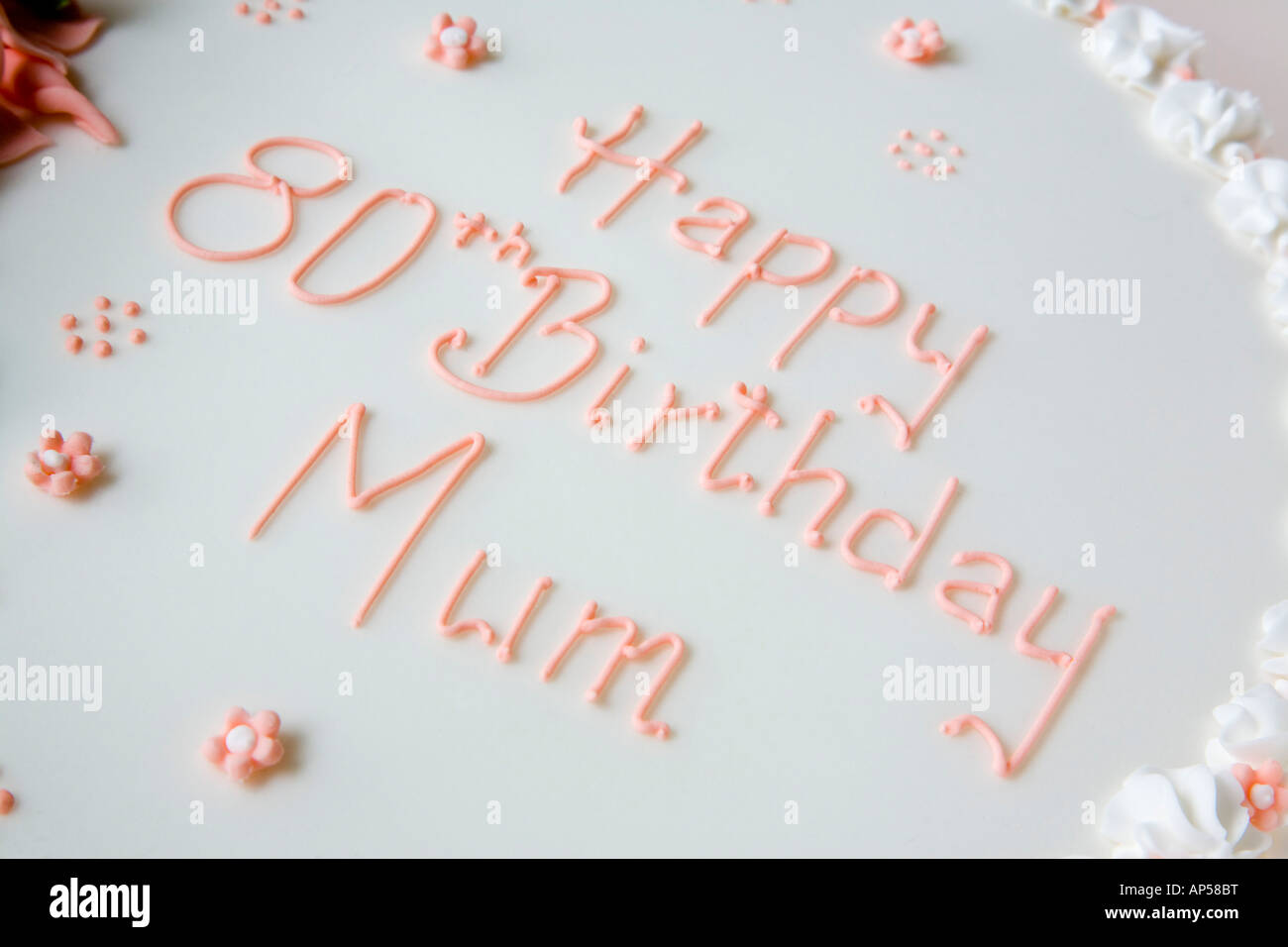 Happy 80th Birthday Mum Cake Decorated With Writing In Pink Piped Icing On White Close Up Diagonal From Above