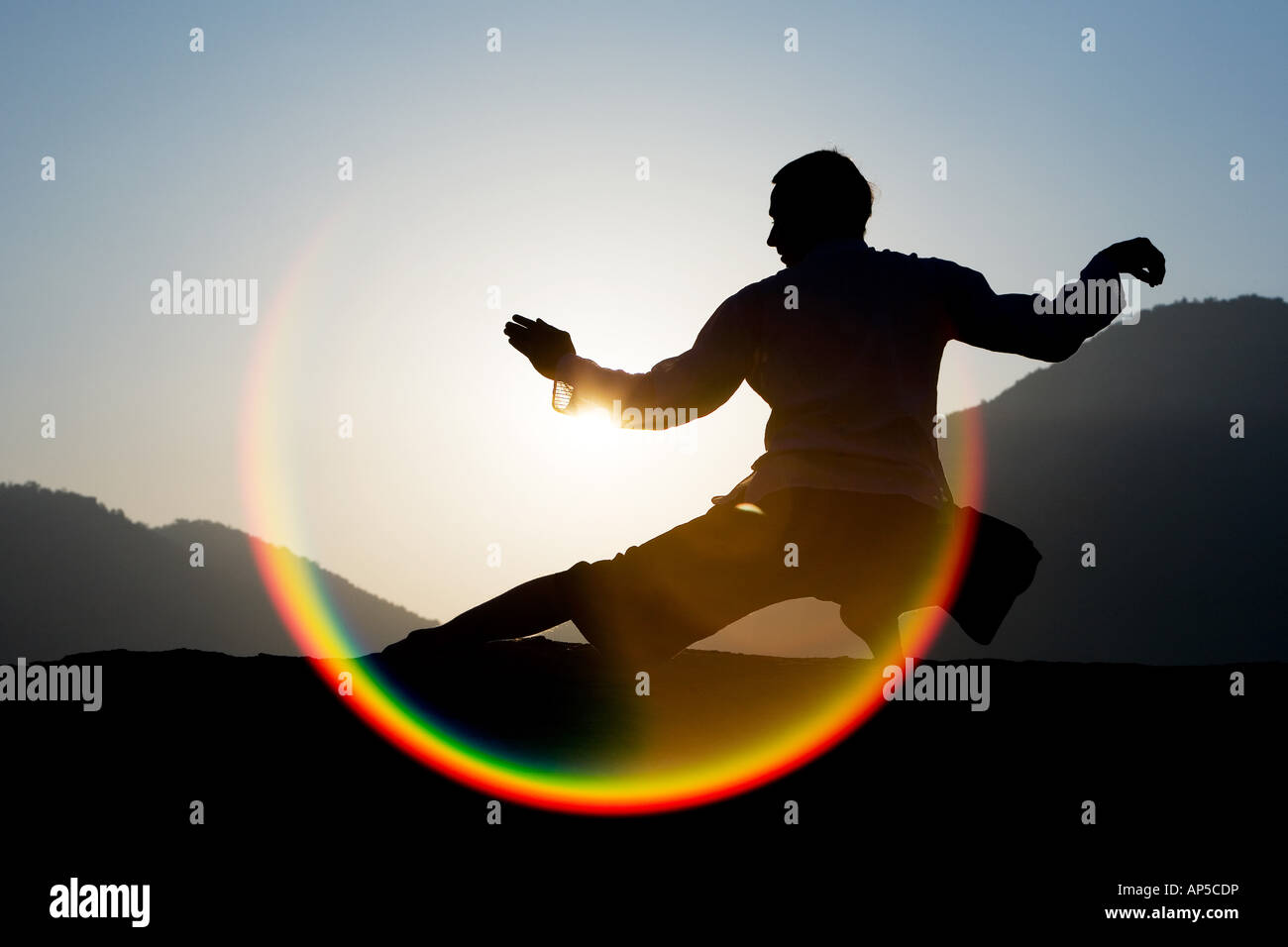 Man performing tai chi against a rising sun in india - Stock Image