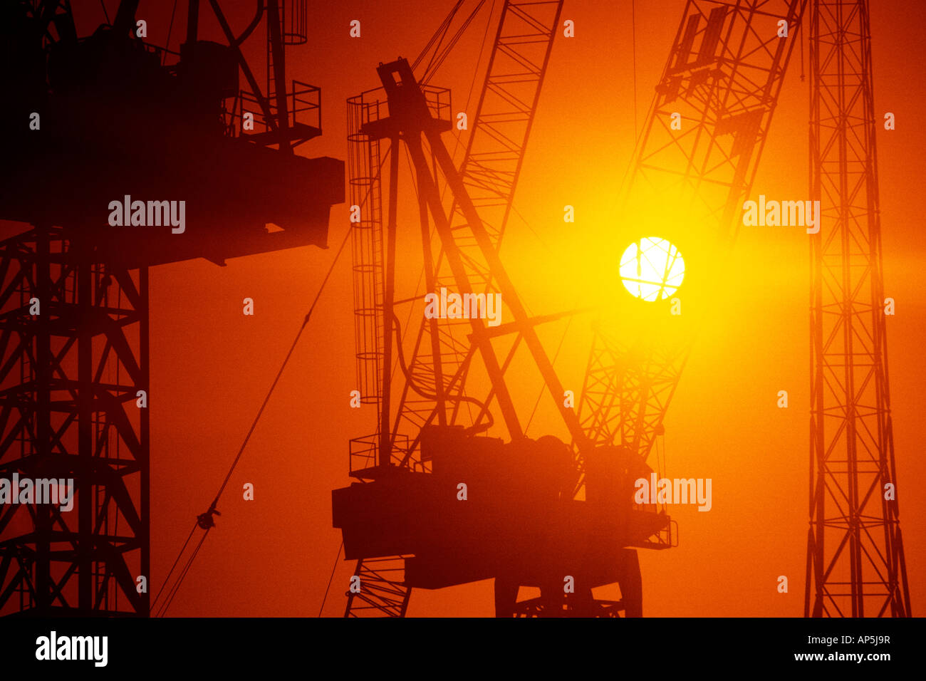 Construction tower cranes at sunset. - Stock Image