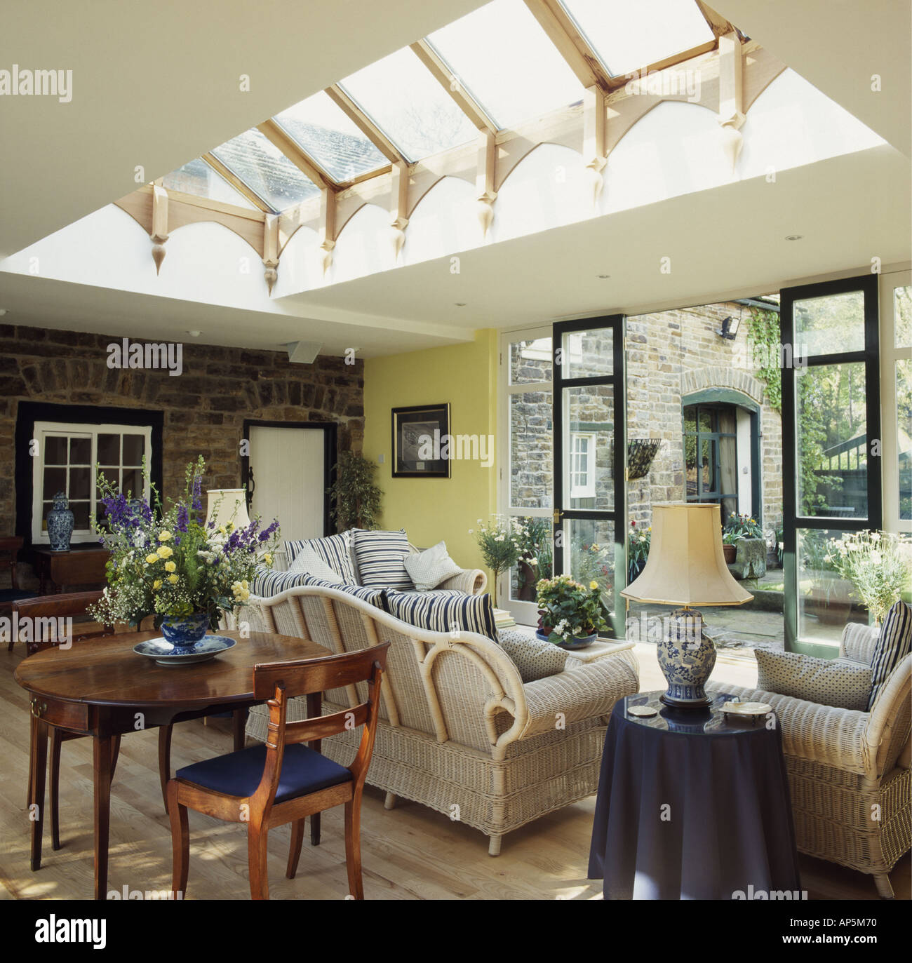 Antique Desk And Chair And Cream Sofa In Sunlit Living Room Extension With  Glass Skylight And Patio Doors