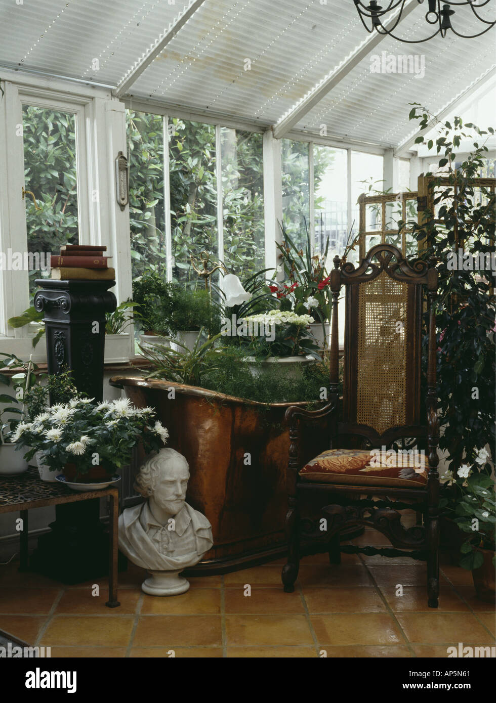 Marble bust and antique Jacobean chair in traditional conservatory filled with green houseplants Stock Photo