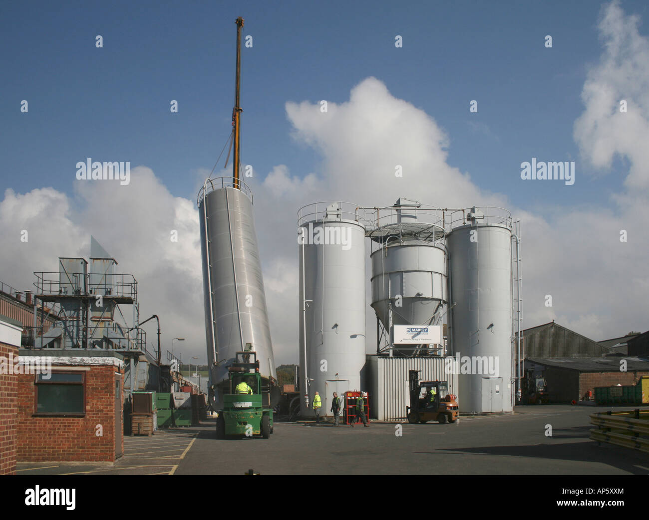 One of a set of 4 large storage silos being lifted by crane prior to its transport to a new location - Stock Image