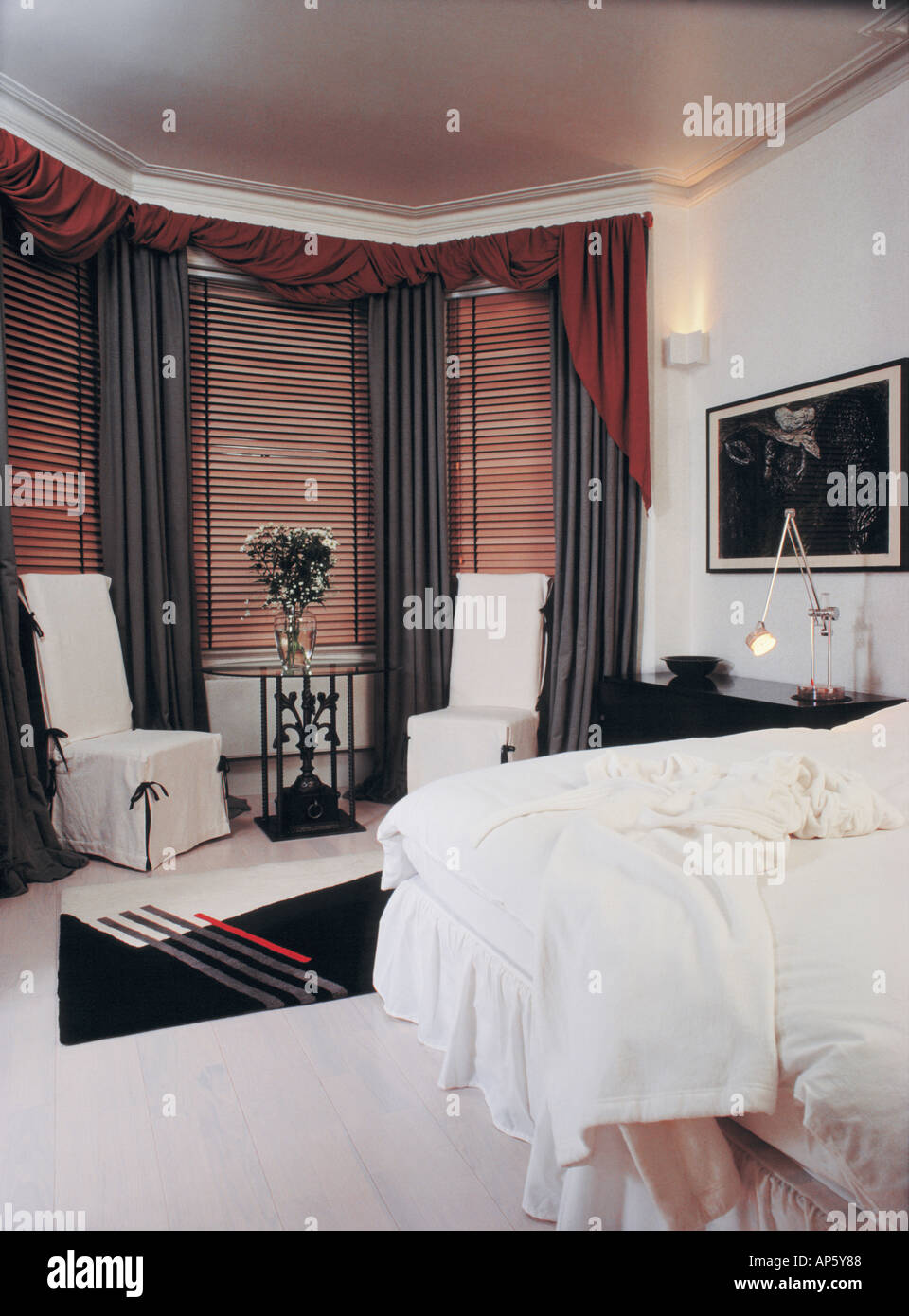 black wooden blinds. White Loosecovers On Chairs Beside Bay Window With Wooden Blinds And Black Curtains In Bedroom Carpet Bedlinen