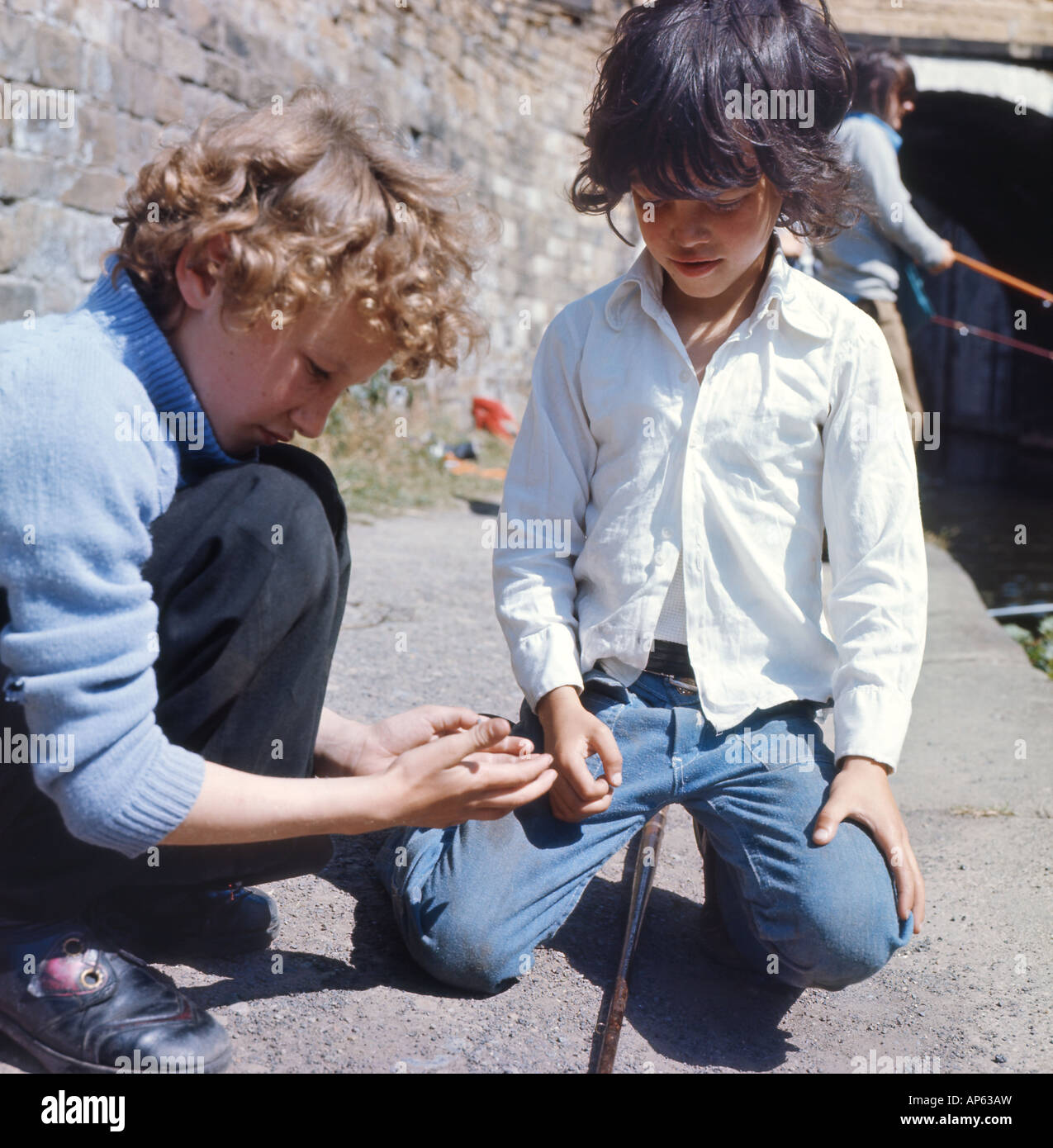 Two boys fishing on the canal in Leeds 1970s England UK  KATHY DEWITT Stock Photo