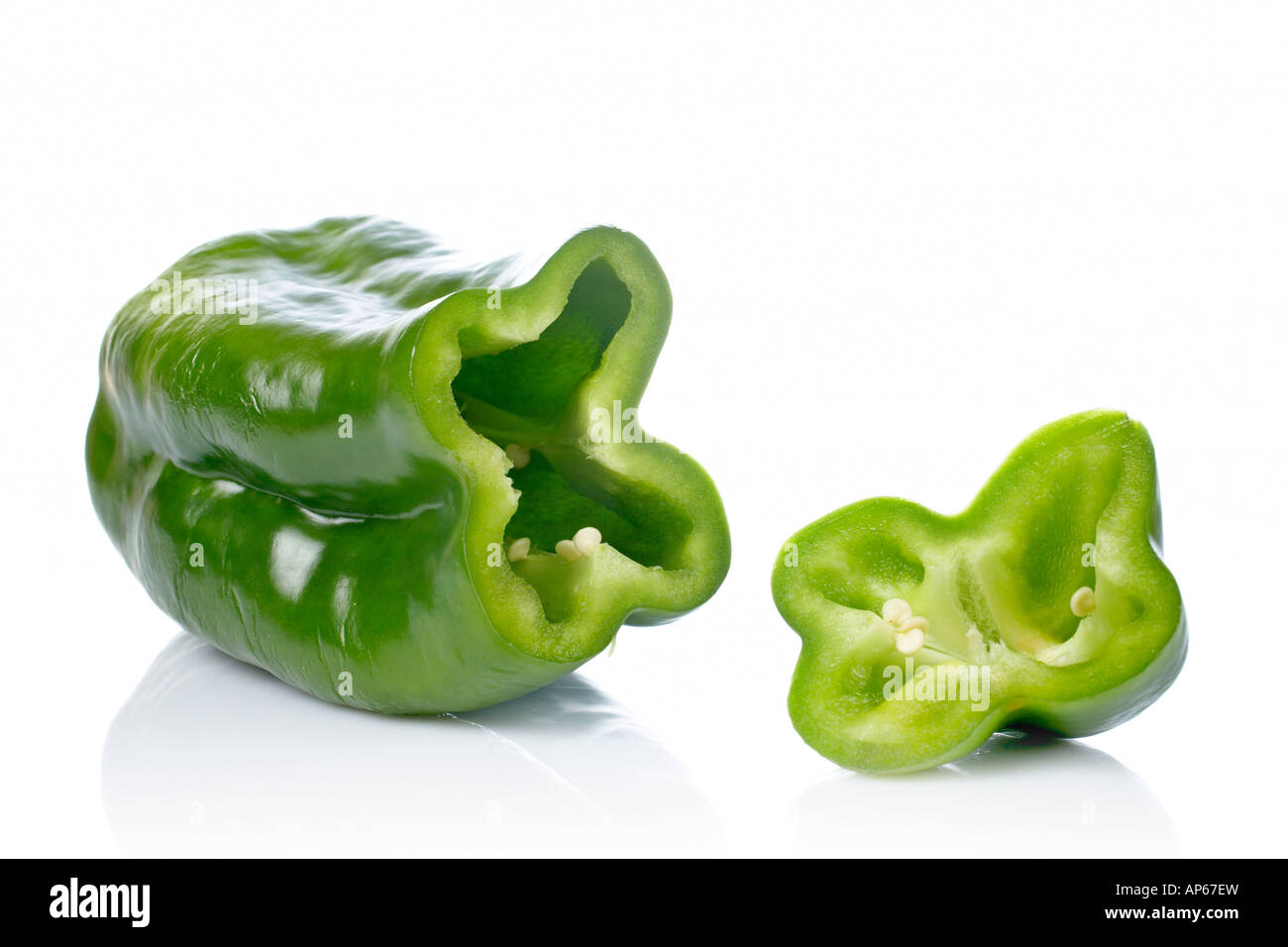 A fresh and tasty green pepper slices reflected on white background Shallow DOF Stock Photo