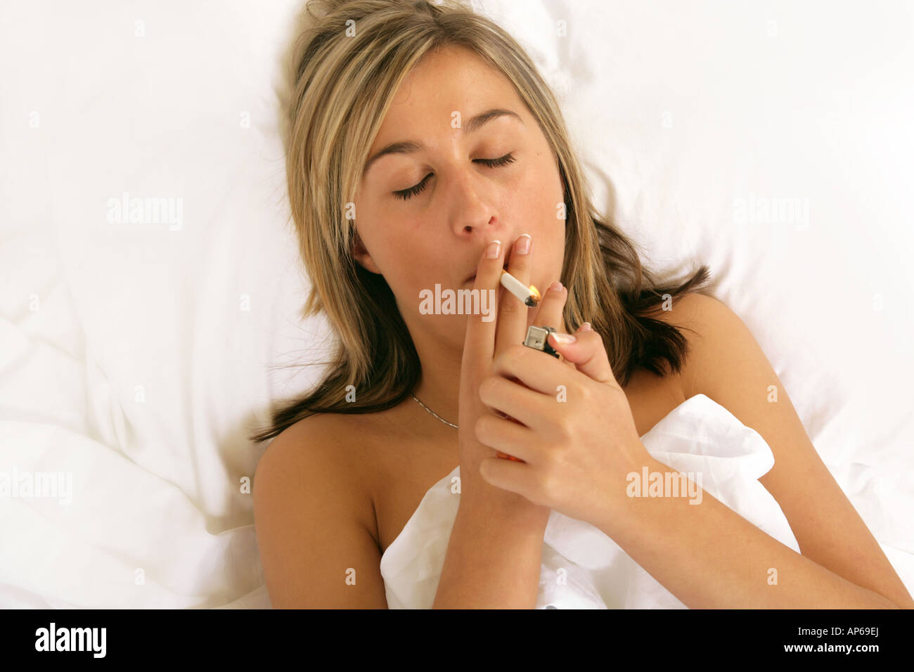 https://c8.alamy.com/comp/AP69EJ/young-woman-smoking-in-bed-lighting-a-cigarette-AP69EJ.jpg