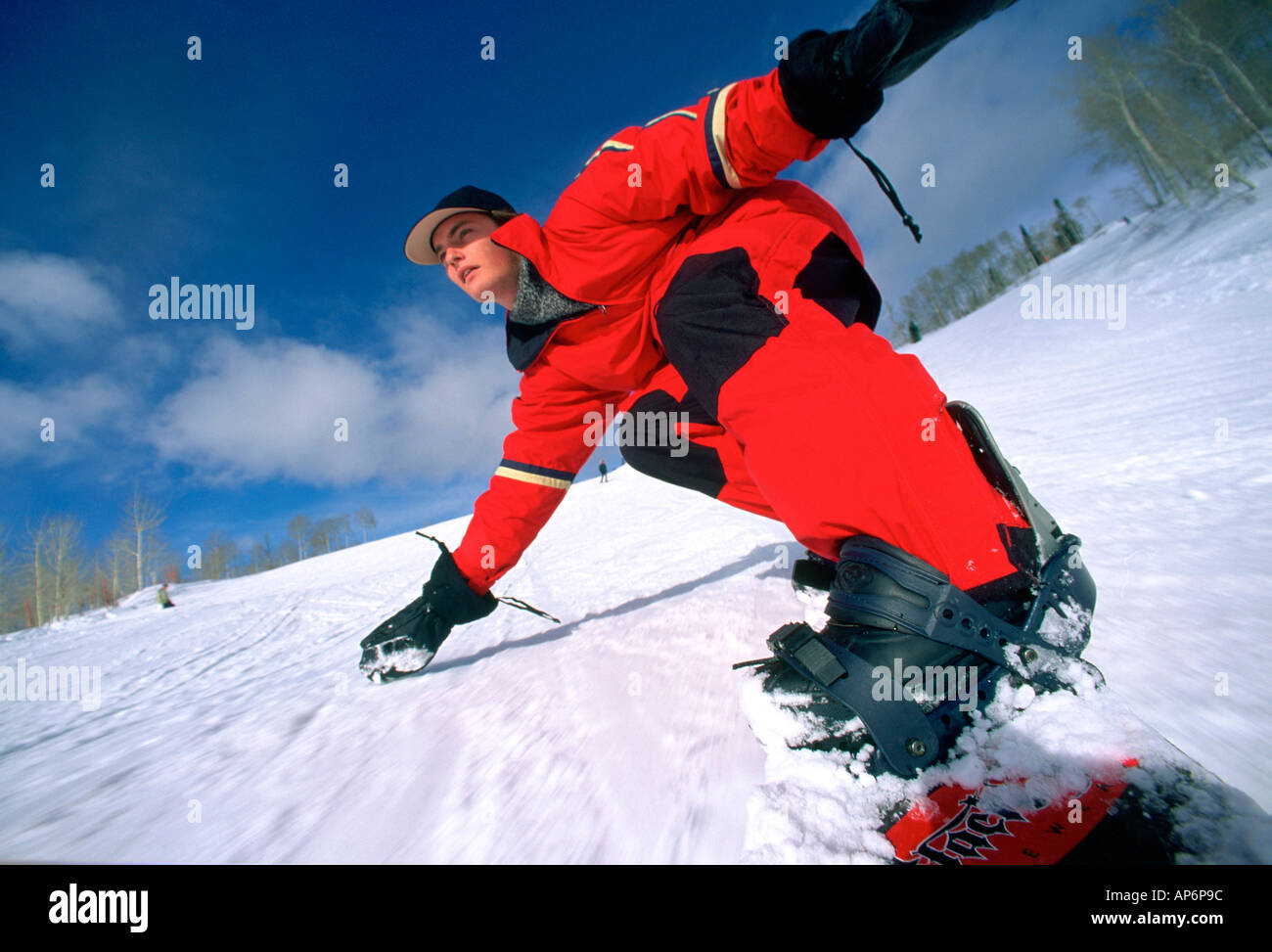 Snowboarder in red skiwear balancing on hand, down-piste, Steamboat Springs, Colorado, USA. - Stock Image