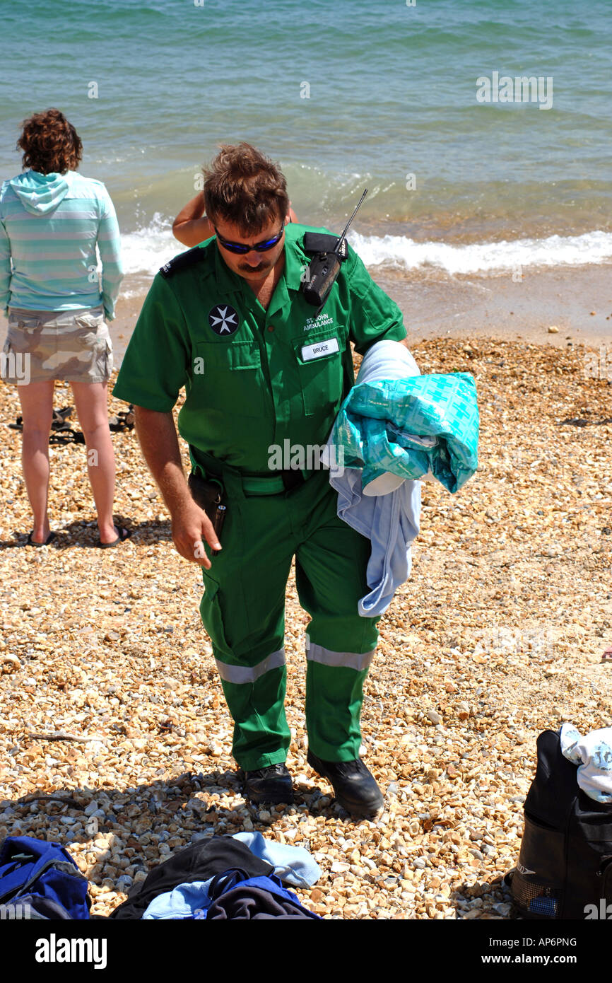 Emergency Paramedic walks up the beach with a blanket in his hand after being called about a possible hyperthermia - Stock Image