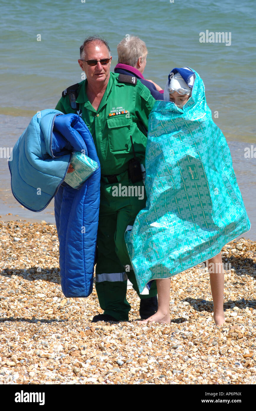 Emergency Paramedic helps a teenage female out of the sea who is suffering from hyperthermia after taking a swim - Stock Image