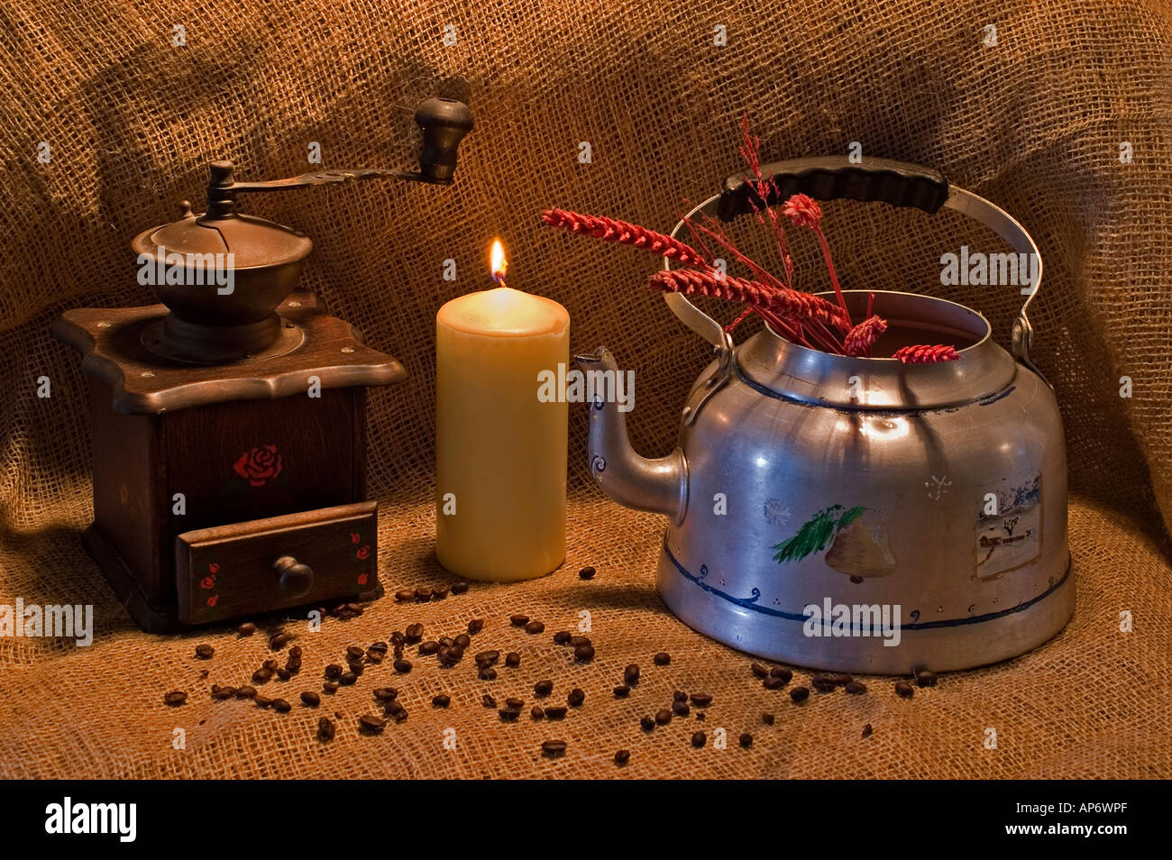 Still life with tin kettle and coffee and coffee mill on a jute background - Stock Image