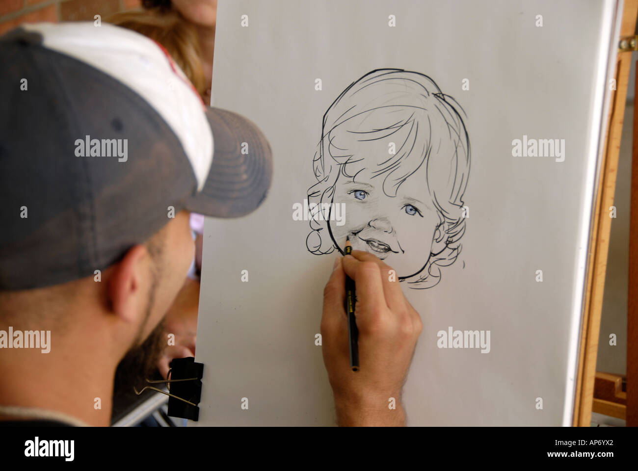 Male sidewalk artist draws a caricature of a mother and daughter - Stock Image